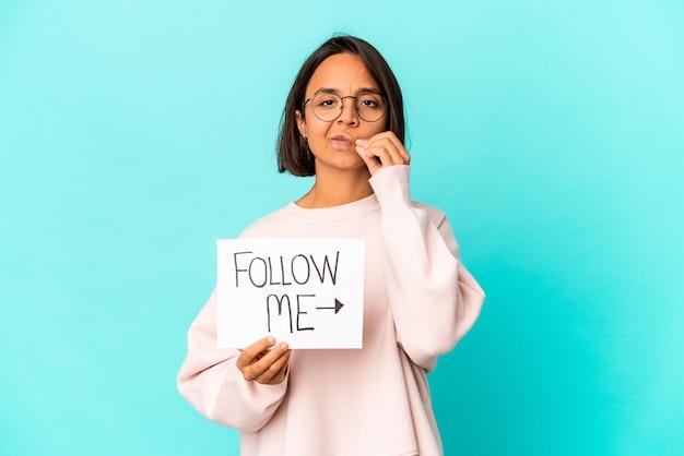 Jeune femme hispanique isolée tenant une pancarte de puissance de fille