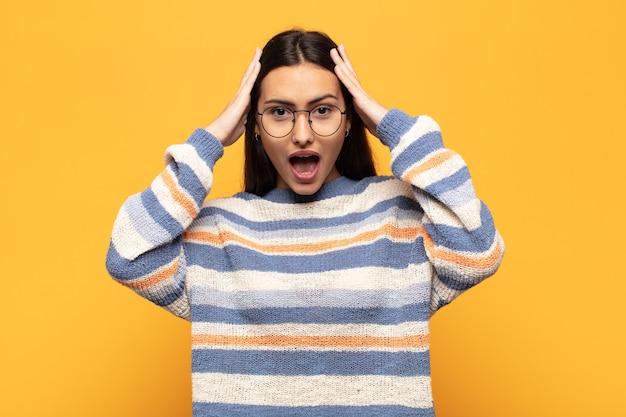 Jeune femme hispanique levant les mains à la tête, bouche bée, se sentant extrêmement chanceux, surpris, excité et heureux