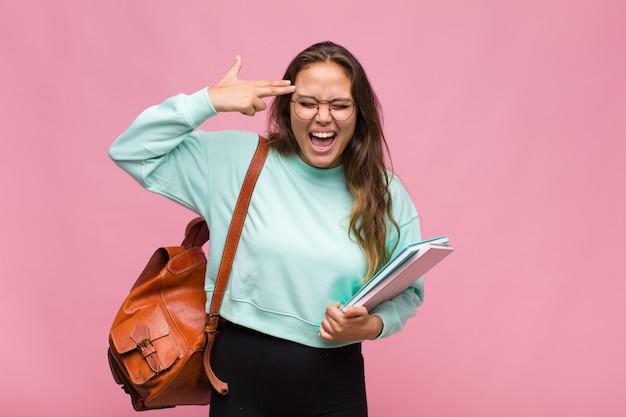 Jeune femme hispanique à la malheureuse et stressée, geste de suicide faisant signe du pistolet avec la main, pointant vers la tête