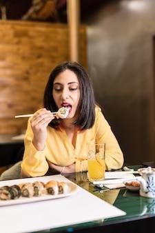 Une jeune femme hispanique mange des sushis dans un restaurant de cuisine japonaise dîner de style de vie pour des amis indépendants et confiants prenant des aliments sains couleur jaune et lavande 2021 ans