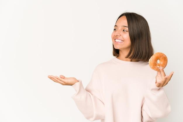 Jeune femme hispanique mangeant un beignet montrant un espace de copie sur une paume et tenant une autre main sur la taille.
