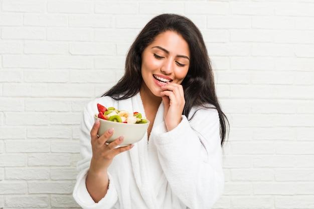 Jeune femme hispanique mangeant un bol de fruits sur le lit
