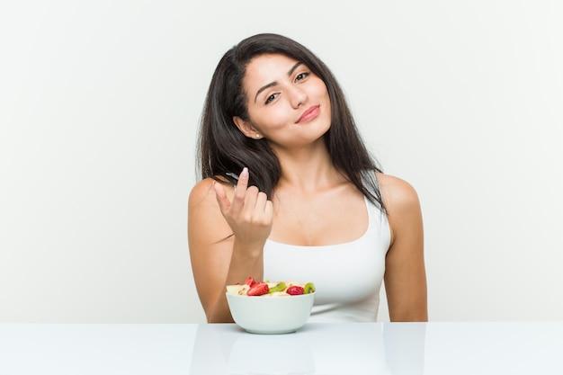 Jeune femme hispanique mangeant un bol de fruits pointant du doigt vers vous, comme si l'invitation se rapprochait.