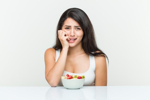 Jeune femme hispanique mangeant un bol de fruits se rongeant les ongles, nerveuse et très inquiète.