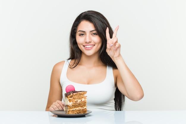 Jeune femme hispanique mangeant un gâteau montrant le signe de la victoire et souriant largement.