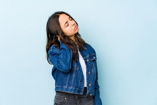 Jeune femme hispanique métisse isolée ayant une douleur au cou due au stress, en massant et en la touchant avec la main.