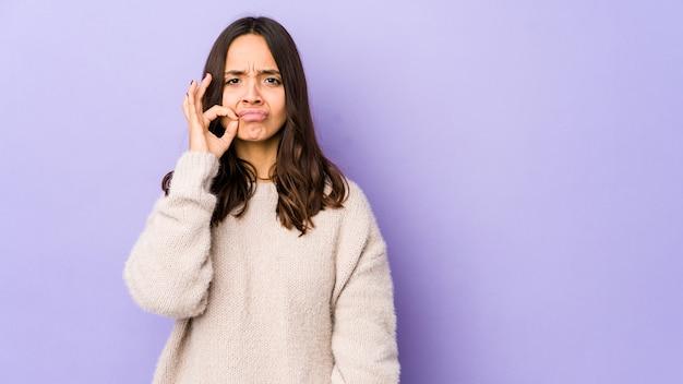 Jeune femme hispanique métisse isolée avec les doigts sur les lèvres en gardant un secret.