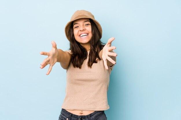 Jeune femme hispanique métisse isolée se sent confiante en donnant un câlin à la caméra.