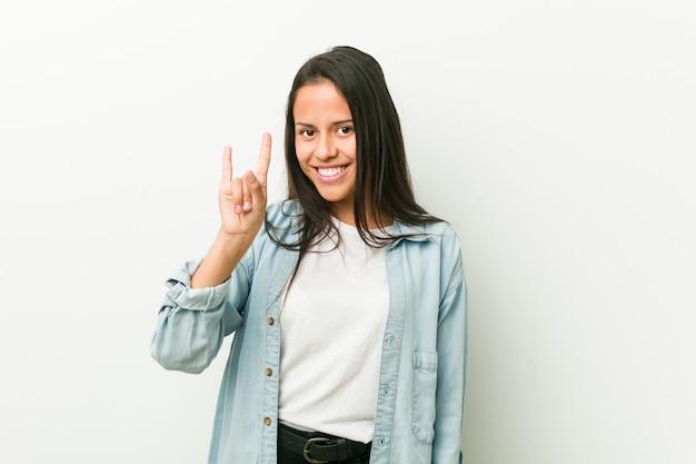 Jeune femme hispanique montrant un geste de cornes