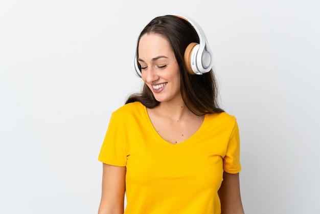 Jeune femme hispanique sur musique d'écoute blanche isolée