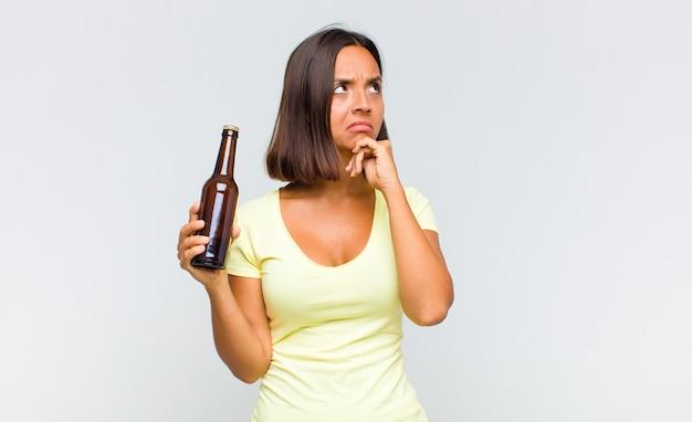 Jeune femme hispanique pensant, doutant et confus, avec différentes options, se demandant quelle décision prendre