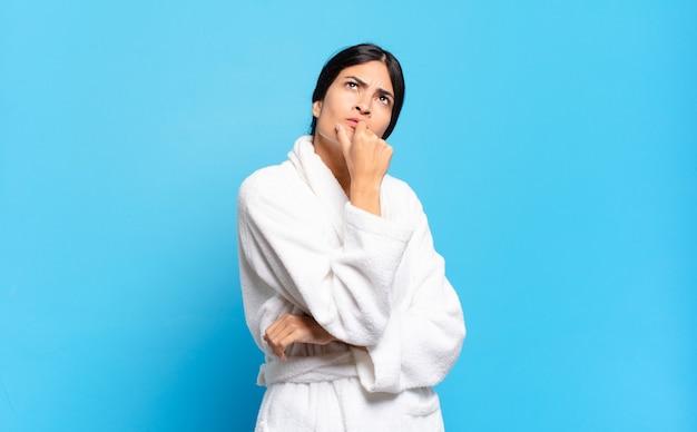 Jeune femme hispanique pensant, se sentant dubitative et confuse, avec différentes options, se demandant quelle décision prendre. concept de peignoir