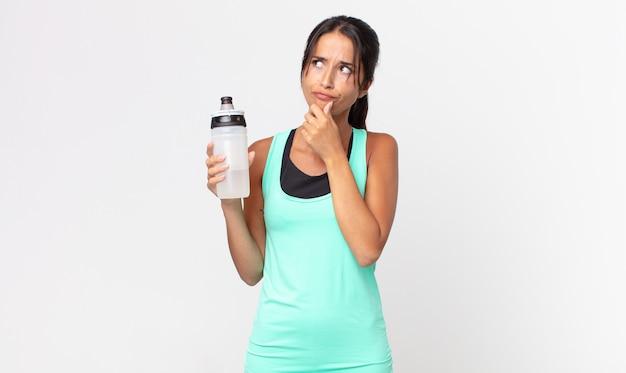 Jeune femme hispanique pensant, se sentant dubitative et confuse et tenant une bouteille d'eau. concept de remise en forme