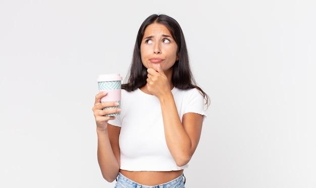 Jeune femme hispanique pensant, se sentant dubitative et confuse et tenant un récipient de café à emporter