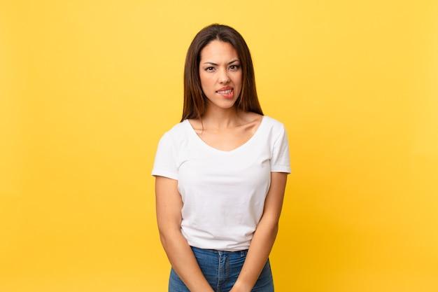 Jeune femme hispanique à la perplexité et confuse