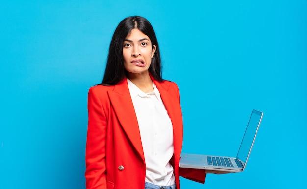 Jeune femme hispanique à la perplexité et à la confusion, mordant la lèvre avec un geste nerveux, ne sachant pas la réponse au problème