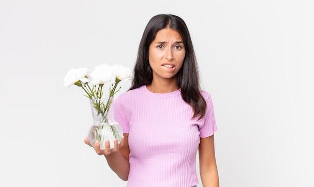 Jeune femme hispanique à la perplexité et à la confusion tenant des fleurs décoratives