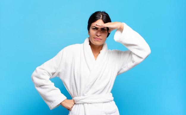Jeune femme hispanique à la perplexité et étonné, avec la main sur le front à la recherche de loin, regarder ou chercher. concept de peignoir