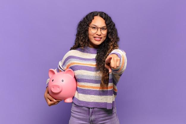 Jeune femme hispanique pointant avec un sourire satisfait, confiant et amical, vous choisissant. concept de tirelire