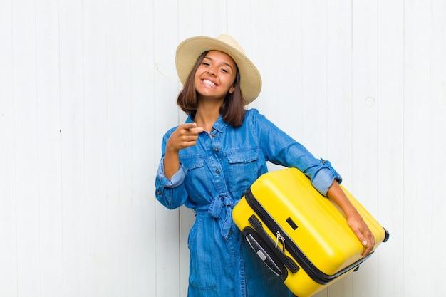 Jeune femme hispanique pointant vers la caméra avec un sourire satisfait, confiant et amical, vous choisissant