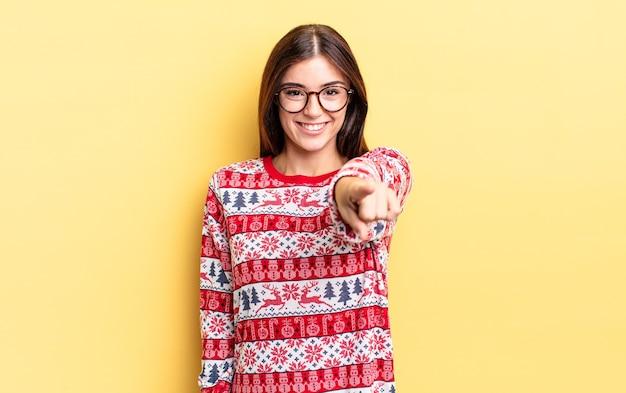 Jeune femme hispanique pointant vers la caméra en vous choisissant. concept de noël et nouvel an