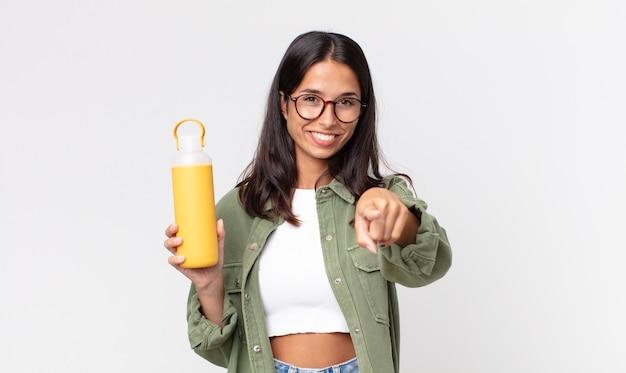 Jeune femme hispanique pointant vers la caméra vous choisissant et tenant un thermos de café