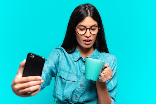 Jeune femme hispanique prenant un café