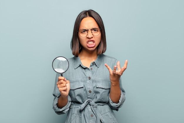 Jeune femme hispanique qui a l'air en colère, agacée et frustrée de crier wtf ou qu'est-ce qui ne va pas avec toi