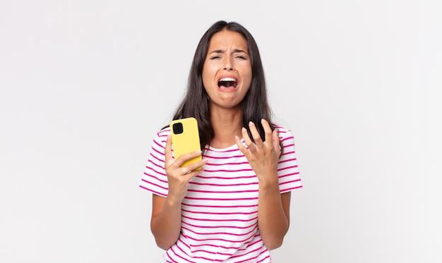Jeune femme hispanique à la recherche désespérée, frustrée et stressée et tenant un smartphone