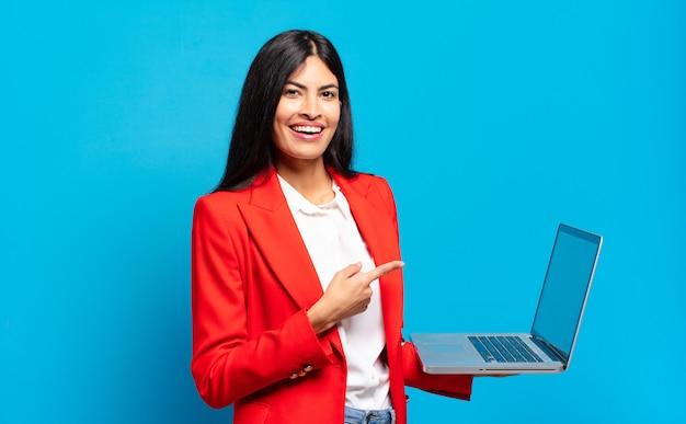 Jeune femme hispanique à la recherche excitée et surprise en pointant vers le côté et vers le haut pour copier l'espace. concept d'ordinateur portable