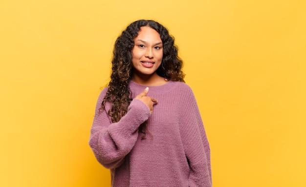Jeune femme hispanique à la recherche heureuse, fière et surprise, pointant joyeusement vers soi, se sentant confiant et noble