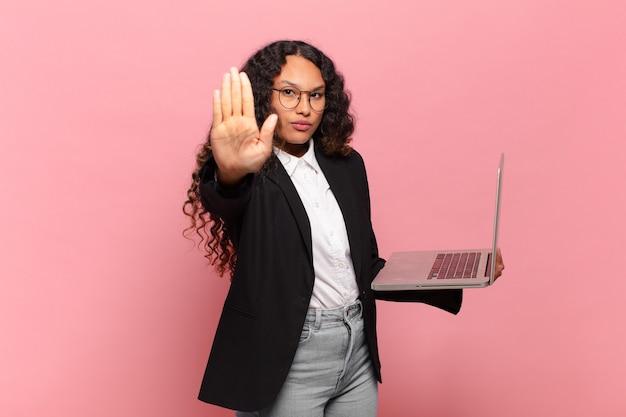 Jeune femme hispanique à la recherche sérieuse, sévère, mécontente et en colère montrant la paume ouverte faisant un geste d'arrêt. concept d'ordinateur portable