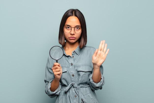Jeune femme hispanique à la recherche de sérieux, sévère, mécontent et en colère montrant la paume ouverte faisant un geste d'arrêt
