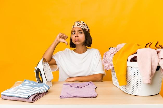 Jeune femme hispanique à repasser les vêtements isolés montrant un geste de dégoût, les pouces vers le bas. concept de désaccord.
