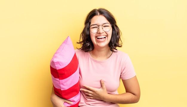 Jeune femme hispanique riant aux éclats d'une blague hilarante. concept de réveil matinal