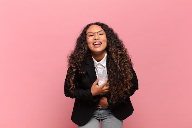 Jeune femme hispanique riant aux éclats d'une blague hilarante, se sentant heureuse et joyeuse, s'amusant. concept d'entreprise