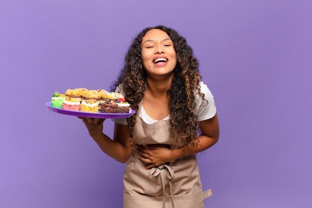 Jeune femme hispanique riant aux éclats d'une blague hilarante, se sentant heureuse et joyeuse, s'amusant