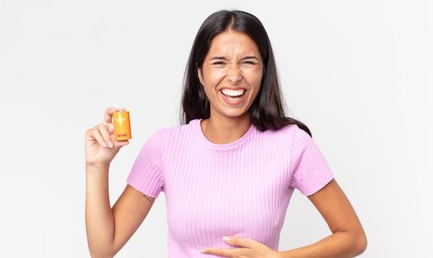 Jeune femme hispanique riant aux éclats d'une blague hilarante et tenant des piles