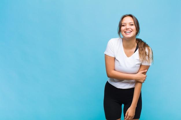 Jeune femme hispanique riant timidement et gaiement, avec une attitude amicale et positive mais peu sûre de soi