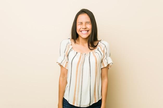 Jeune femme hispanique rit et ferme les yeux, se sent détendue et heureuse.