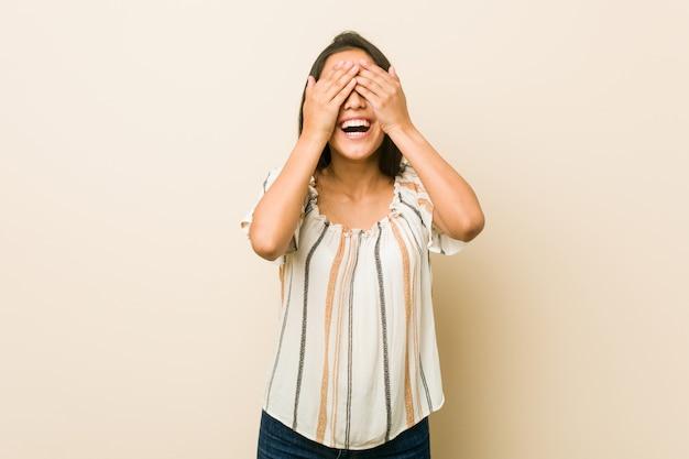 Une jeune femme hispanique se couvre les yeux des mains, sourit largement en attendant une surprise.