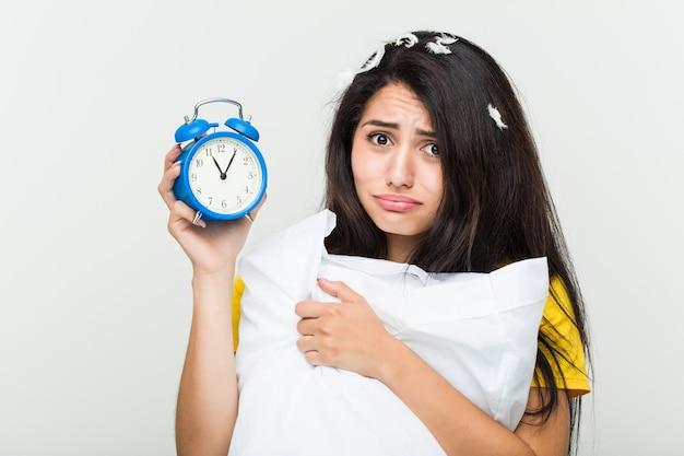 Jeune femme hispanique se réveiller tenant un oreiller et un réveil