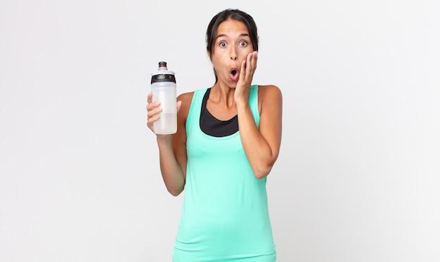 Jeune femme hispanique se sentant choquée et effrayée et tenant une bouteille d'eau. concept de remise en forme