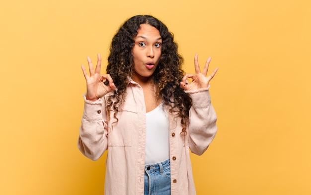 Jeune femme hispanique se sentant choquée, étonnée et surprise, montrant son approbation en faisant signe d'accord avec les deux mains