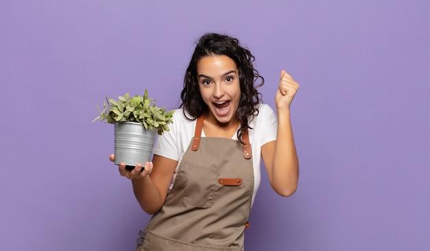 Jeune femme hispanique se sentant choquée, excitée et heureuse, riant et célébrant le succès, disant wow!