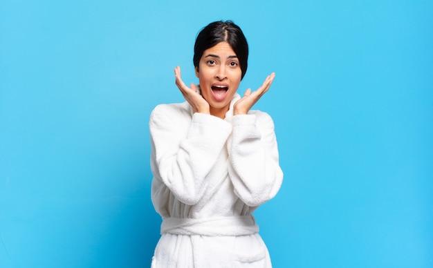 Jeune femme hispanique se sentant choquée et excitée, riant, étonnée et heureuse à cause d'une surprise inattendue. concept de peignoir