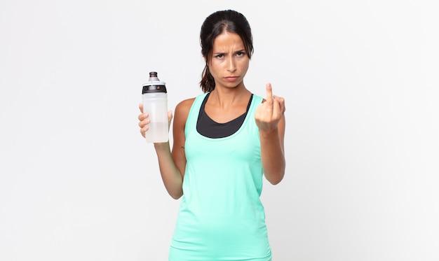 Jeune femme hispanique se sentant en colère, agacée, rebelle et agressive et tenant une bouteille d'eau. concept de remise en forme