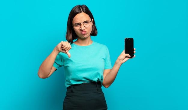 Jeune femme hispanique se sentant en colère, en colère, ennuyée, déçue ou mécontente, montrant les pouces vers le bas avec un regard sérieux
