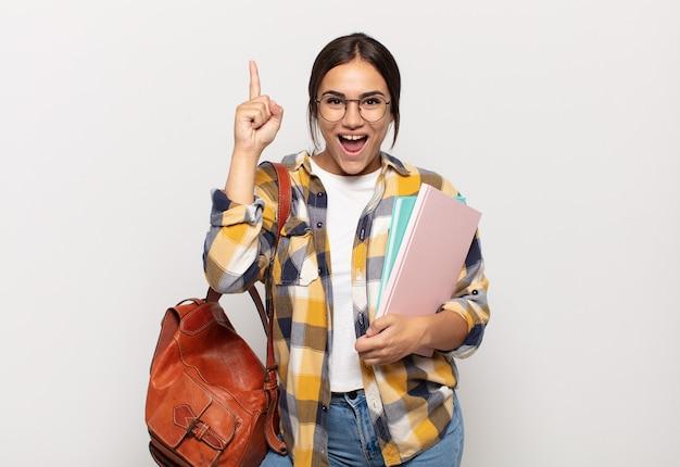 Jeune femme hispanique se sentant comme un génie heureux et excité après avoir réalisé une idée