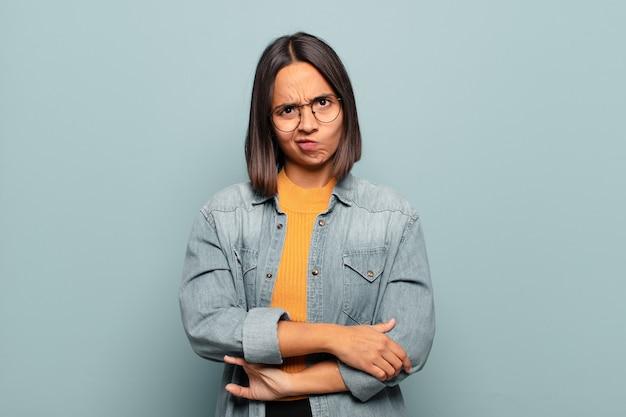Jeune femme hispanique se sentant confuse et douteuse, se demandant ou essayant de choisir ou de prendre une décision